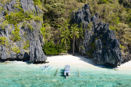 View from above, stunning aerial view of the Entalula Beach, a white sand beach surrounded by rocky formations and bathed by a crystal clear sea. Entalula island, Bacuit Bay, El Nido, Palawan, Philippines.