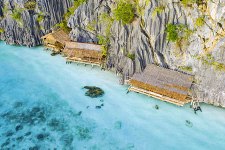 View from above, stunning aerial view of some bungalows surrounded by rocky cliffs bathed by a turquoise, crystal clear sea. Malwawey Coral Garden, Coron Island, Palawan, Philippines.