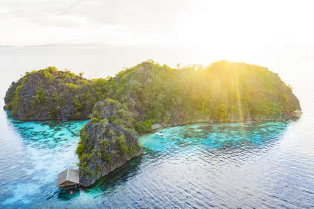 View from above, stunning aerial view of a small island bathed by a turquoise, crystal clear sea during a beautiful sunset. Malwawey Coral Garden, Coron Island. Palawan, Philippines.