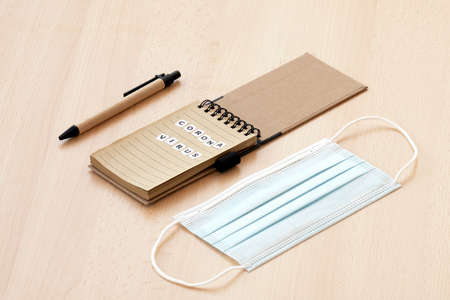 """Flat lay with copy space. A face mask, a spiral notepad with """"Coronavirus"""" written on it and a pen are arranged on a wooden table. Coronavirus disease (COVID-19) is an infectious disease caused by a newly discovered coronavirus."""