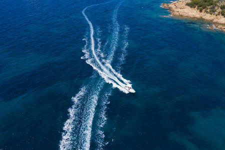 View from above, stunning aerial view of a small boat sailing on a beautiful turquoise sea that bathes the green and rocky coasts of Sardinia. Emerald Coast (Costa Smeralda) Italy