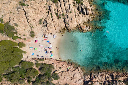 View from above, stunning aerial view of a small beach with beach umbrellas and people swimming in a turquoise clear water, Cala Coticcio, (Tahiti), La Maddalena Archipelago, Sardinia, Italy. Archivio Fotografico
