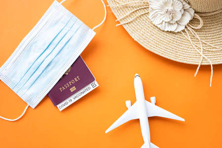 Flat lay, an aircraft model, sun hat, protective face mask and a passport with 'Covid-19 Vaccinated' label inside are arranged on an orange background. Travel concept during the Covid-19 pandemic.