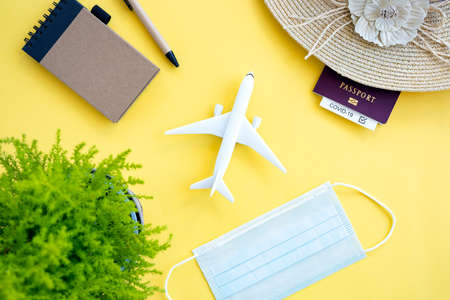Flat lay, an aircraft model, sun hat, protective face mask, plant, passport and a notepad with a pen are arranged on a yellow background. Travel concept during the Covid-19 pandemic