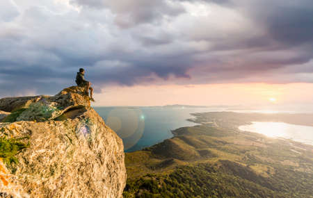 Stunning view of a boy enjoying a beautiful sunset sitting on top of a mountain, Golfo Aranci, Sardinia, Italy.