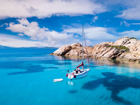 View from above, stunning aerial view of a sail boat sailing in front of Mortorio island during a sunny day. Mortorio is a small island bathed by a turquoise and transparent water.
