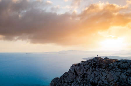 View from above, stunning aerial view of a person enjoying a beautiful sunset from the summit of a mountain, Golfo Aranci, Sardinia, Italy.