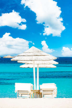 (Selective focus) Stunning view of some white thatch umbrellas and sunbeds on a white sand beach bathed by a beautiful, turquoise sea. Romazzino Beach, Porto Cervo, Sardinia, Italy.