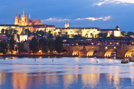 st charles: Pretty night time illuminations of Prague Castle, Charles Bridge and St Vitus Cathedral reflected in the Vltava river running through the heart of the city of Prague in the Czech Republic. Stock Photo