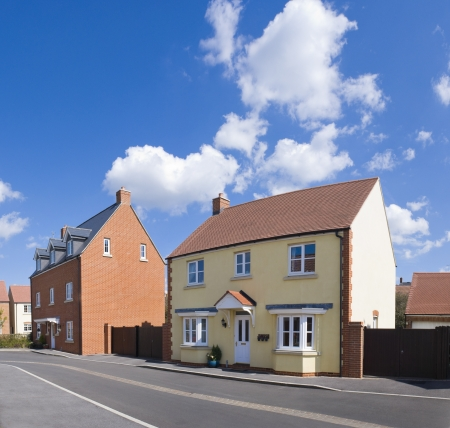 detached: Pretty newly built homes and gardens against a clear blue summers sky. Stock Photo