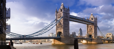 Magnificent Victorian Tower Bridge of London built in 1894 still stands as a symbol of the city. Converted brick warehouses and Thames beach and river.