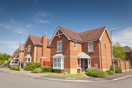 uk: Pretty newly built homes and gardens against a clear blue summers sky. Stock Photo