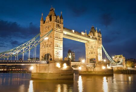Magnificent Victorian Tower Bridge of London built in 1894 still stands as a symbol of the city  Converted brick warehouses and Thames beach and river illuminated by pretty night time lights  photo