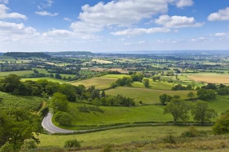 cotswold: Idilliaco rurale vista della bella terreni agricoli con soffici nuvole bianche, nella splendida cornice del Cotswolds, Inghilterra, Regno Unito