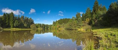 Ciel bleu et les eaux du lac calme qui reflète la jolie verdure de la campagne des Cotswolds piqué image panoramique détaillée lors vu grand