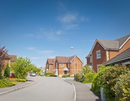 Jolie maisons nouvellement construites et les jardins contre un ciel bleu clair étés