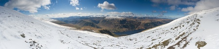 Dramatic snow covered mountains of Helvellyn and winter blue skies, Lake District, England, UK. Stitched panorama, detailed when viewed large. Stock Photo - 19829731