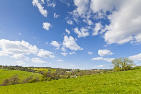 Idyllic rural view of pretty farmland with white fluffy clouds, in the beautiful surroundings of the Cotswolds, England, UK.