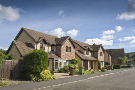 Vrij nieuw gebouwde huizen en tuinen tegen een heldere blauwe zomershemel.
