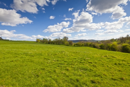 Idyllic rural view of pretty farmland with white fluffy clouds, in the beautiful surroundings of the Cotswolds, England, UK. photo