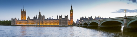 london skyline: Chrome blue sky reflections over the neo-gothic Houses of Parliament, iconic Big Ben (1834) and sweeping arches of Westminster bridge in the heart of london. Stock Photo