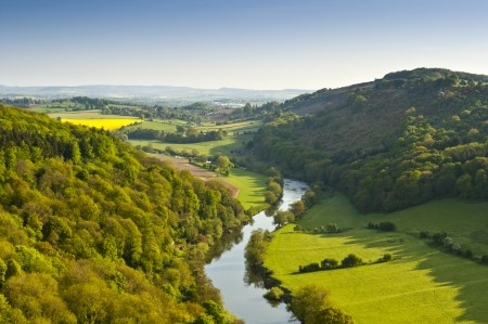 Meandering River Wye making its way through lush green rural farmland in the warm early sunlight.