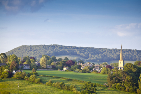 village house: Idyllic rural view of gently rolling patchwork farmland and villages with pretty wooded boundaries, in the beautiful surroundings of the Cotswolds, England, UK.