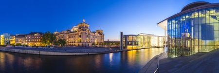 Mighty Reichstag parliament (1894), apartments and Bundeskanzleramt the German chancellery illuminated at night and reflected in the river Spree, Berlin, Germany. Stock Photo