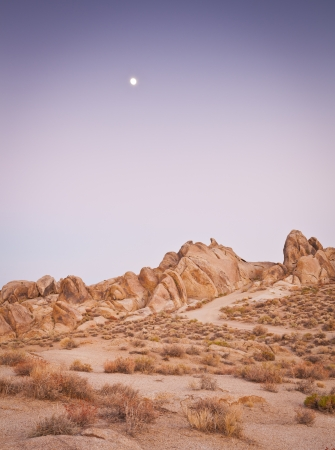 Salmon pink hues of sunset illuminate the weird and wonderful rock formations of the Alabama Hills in California, which is a popular filming location for television and movie productions. photo