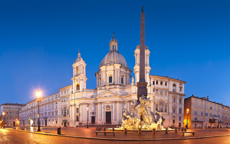 Fountain of the Four Rivers (1651) overlooked by the church of SantAgnese in Agone in the beautifully Baroque Piazza Navona (1651) illuminated by pretty streelights. photo