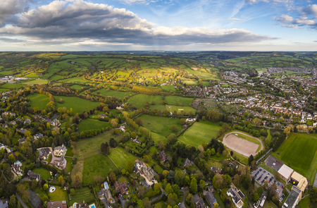 Dramatic aerial view of idyllic rolling patchwork farmland and houses with pretty wooded boundaries, lit in warm early evening sunshine in the heart of the Cotswolds, England, UK. Stock Photo