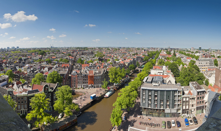 anne: Amsterdam blue sky view over city rooftops, pretty tree lined Prinsengracht canal and Anne Frank House  right