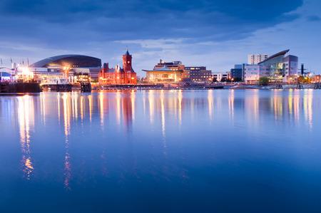 Iluminaciones nocturnas Pretty de la impresionante bahía de Cardiff, muchos lugares visibles, incluyendo el edificio Pierhead (1897) y la Asamblea Nacional de Gales.