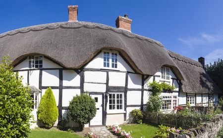 thatched house: Pretty country village scenic of traditional thatched cottages and pristine gardens. Stitched panoramic image.