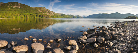 lake district: Summer woodland at Derwent Water with dramatic Latrigg mountain backdrop in the beautiful English Lake District  Stitched panoramic image detailed when viewed large
