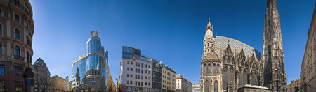 stephansplatz: Dramatic sweeping panoramic of Stephansplatz with a view of Viennas famous St Stephens Cathedral built in 1147 with its colorful mosaic roof and the modern Haas Haus shopping complex. Stock Photo