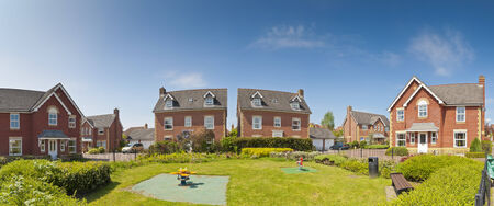residential home: Pretty newly built homes and gardens against a clear blue summers sky. Stitched panoramic image detailed when viewed large.