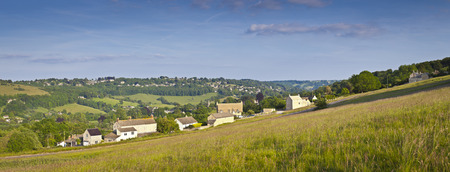 Idyllic rural view of gently rolling patchwork farmland and villages with pretty wooded boundaries, in the beautiful surroundings of the Cotswolds, England, UK. Stitched panoramic image. photo