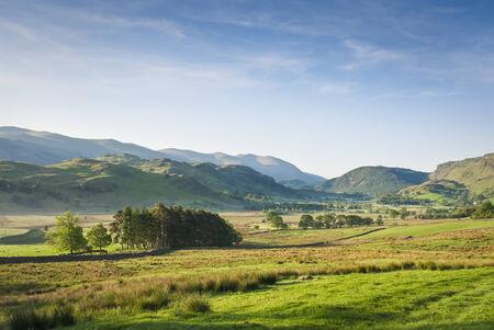 cumbria: Warm misty morning light illuminating idyllic rural landscape of gently rolling hills, dry stone walls and pretty woodland, Lake District, Cumbria, UK. Stock Photo