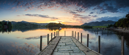 Inviting jetty leading to a dramatic sunset reflected in a perfectly still Derwent Water, Lake District, UK