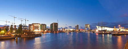 Night time illuminations of the thriving City regeneration in Oosterdock, Amsterdam. Visible are the city library, science centre and numerous skyscrapers in various stages of completion. photo