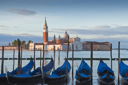 Beautiful San Giorgio Maggiore church, traditional gondolas and street lamps illuminated in the early morning. photo