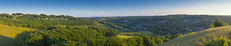 severn: Idyllic rolling patchwork farmland with pretty wooded boundaries, lit in warm early evening sunshine in the heart of the Cotswolds, England, UK. Stitched panoramic image.