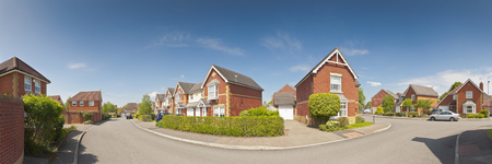 Pretty newly built homes and gardens against a clear blue summers sky  Stitched panoramic image detailed when viewed large  Stock Photo