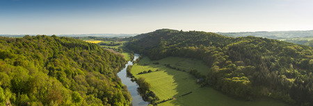yat: Meandering River Wye making its way through lush green rural farmland in the warm early sunlight