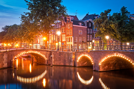 Pretty dutch doll houses illuminated and reflected along the tranquil canals of Amsterdam. photo