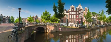 예쁜 네덜란드어 인형 하우스와 하우스 보트는 암스테르담, 네덜란드의 고요한 운하에 반영.