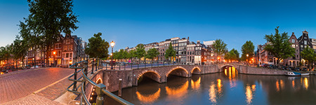 Pretty dutch doll houses illuminated at night and reflected in the tranquil canals of Amsterdam. Stock Photo