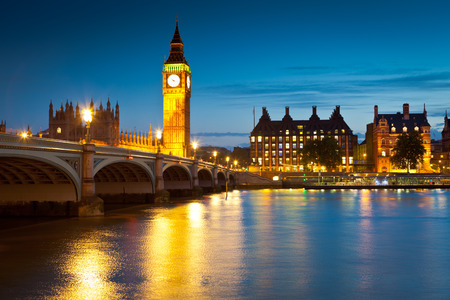 Chrome blue sky reflections over the neo-gothic Houses of Parliament, iconic Big Ben (1834) and sweeping arches of Westminster bridge in the heart of london. photo