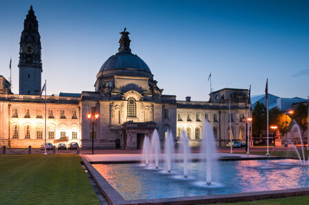 Cardiff City Hall (1906) and fountains at night in the heart of the capital, city Museum to the right. Stock Photo